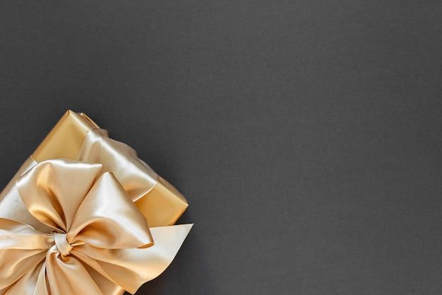 Pudełko ze złotą wstążką i kokardą na czarnym tle