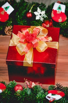 Pudełko ze złotym kolorem wstążki na tle drewna z choinką i tradycyjnymi ozdobami rekwizyty bożonarodzeniowe. koncepcja szczęśliwego i radosnego festiwalu.