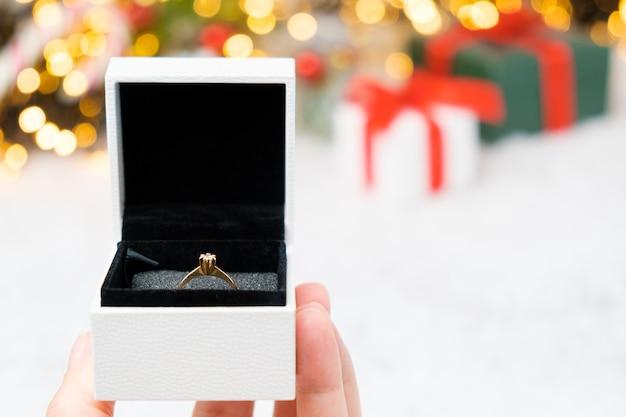 Pudełko ze złotym pierścieniem na śniegu w tle bożego narodzenia