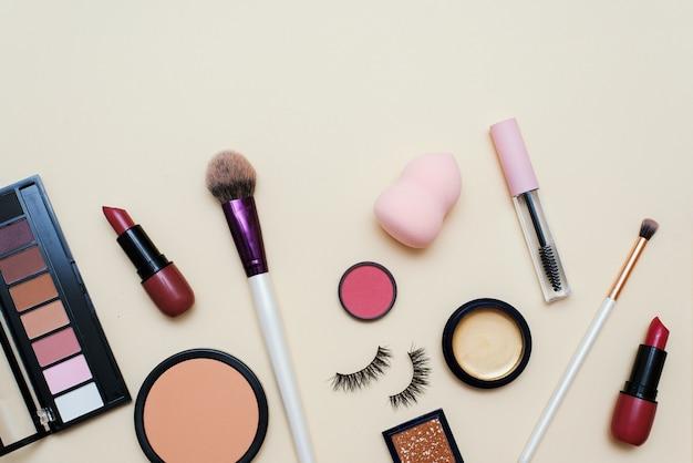 Puder do twarzy, pędzel i różne kosmetyki do makijażu dekoracyjnego na kolorowym tle