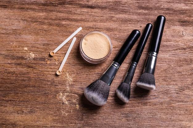 Puder mineralny w cielistych kolorach z łyżeczką do makijażu na drewnianym tle