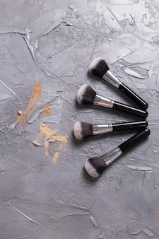 Puder mineralny w różnych kolorach z pędzlami do makijażu na drewnianym tle, widok z góry