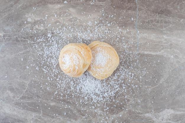 Puder waniliowy i dwa kruche ciasteczka na marmurowej powierzchni