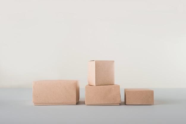 Pudła kartonowe na białej przestrzeni. ekologiczne opakowania produktów papierniczych z bliska i kopia przestrzeń. pojemniki rzemieślnicze, opakowania, pudełka, opakowania.