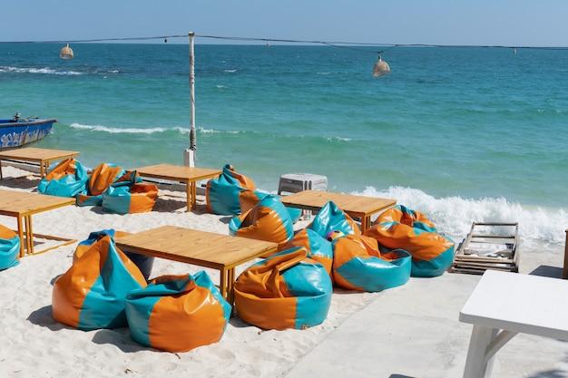 Pufy i stół na plaży.