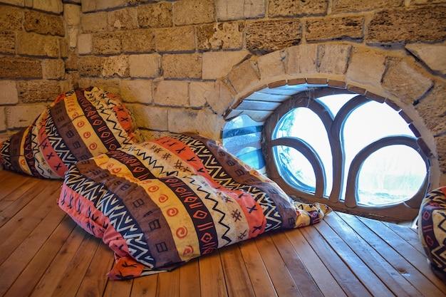 Pufy w afrykańskim kolorze leżące w rogu na drewnianej podłodze przy oknie z niezwykłą kratą