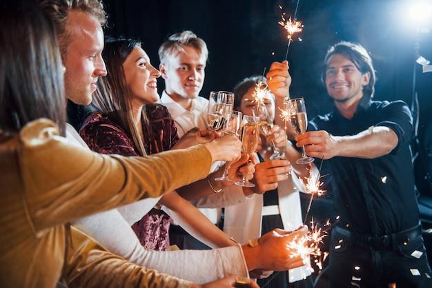 Pukające okulary. grupa wesołych przyjaciół z okazji nowego roku w pomieszczeniu z napojami w rękach.