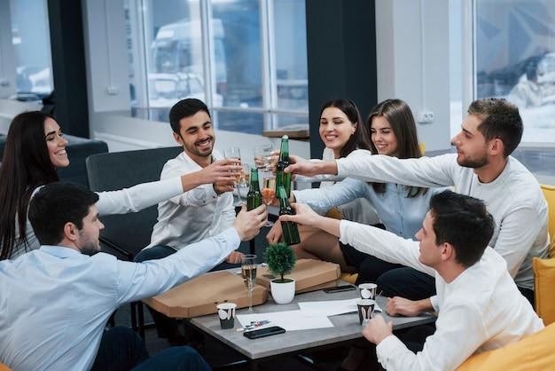 Pukanie do butelek i szklanek. świętowanie udanej transakcji. młodzi urzędnicy siedzący przy stole z alkoholem