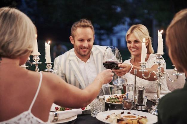 Pukanie do kieliszków wina. grupa przyjaciół w eleganckim stroju ma luksusowy obiad