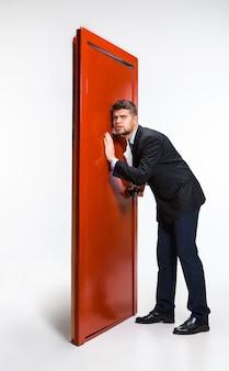 Pukanie w pustkę. młody mężczyzna w czarnym garniturze próbuje otworzyć czerwone drzwi na drabinie kariery, ale są zamknięte. brak motywacji. pojęcie kłopotów pracownika biurowego, biznesu, problemów, stresu.