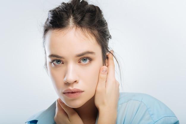Pułapka emocjonalna. brunetka, wrażliwa, atrakcyjna kobieta kładzie rękę na uchu, patrząc w kamerę i pozując na odosobnionym tle