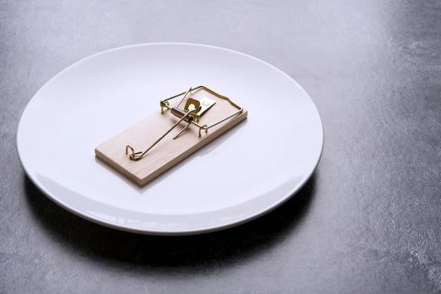 Pułapka na myszy leży na białym talerzu