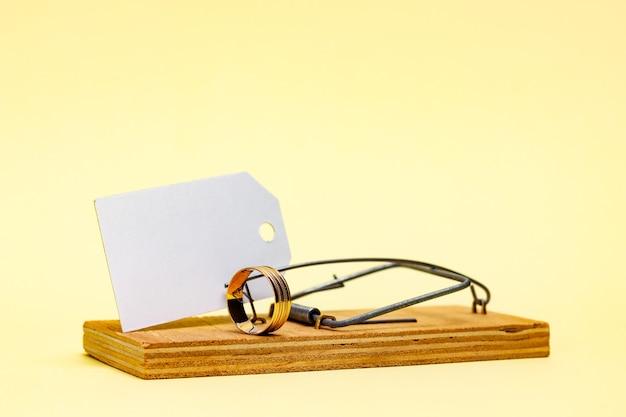 Pułapka na myszy z obrączką i białą kartką z miejscem na tekst. małżeństwo dla pozoru, małżeństwo oszustów. zdjęcie wysokiej jakości