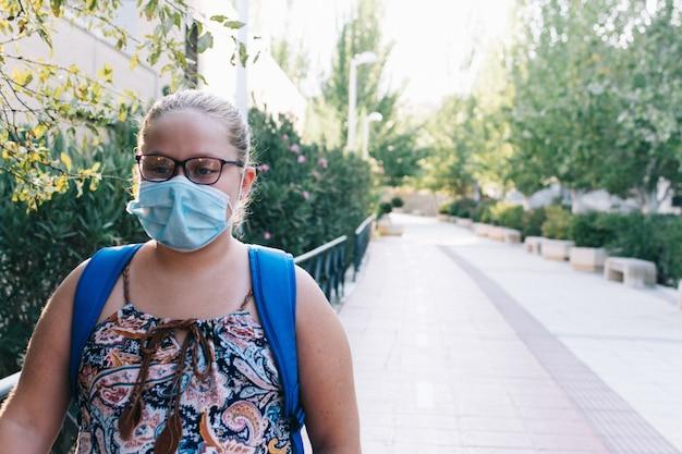 Pulchna blondynka w okularach, niebieskim plecaku i masce w drodze do szkoły