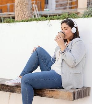 Pulchne dziewczyny ciesząc się kawą na świeżym powietrzu