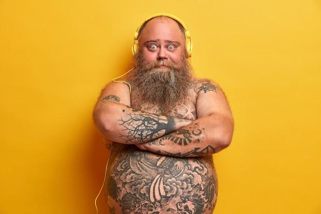 Pulchny męski meloman stoi z założonymi rękami, wygląda pewnie, ma wytatuowane ciało, słucha muzyki w słuchawkach, gęstą brodę i wąsy, duży, gruby brzuch, odizolowany na żółtej ścianie