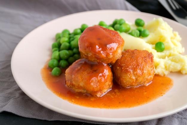 Pulpety w słodko-kwaśnym sosie pomidorowym z puree ziemniaczanym.