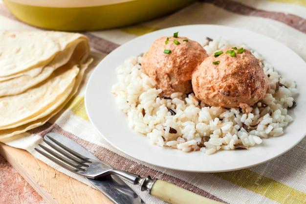 Pulpety z kurczaka w kremowym sosie pomidorowym z ryżem na białym talerzu