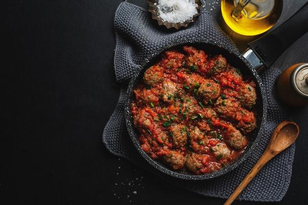 Pulpety z sosem pomidorowym podawane na patelni na ciemnym tle.