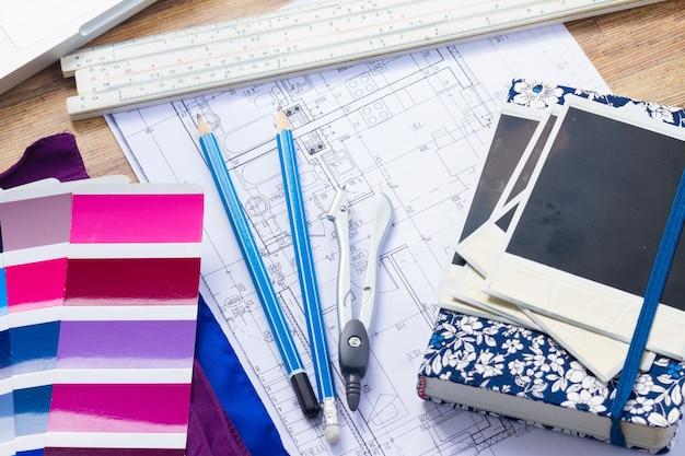 Pulpit roboczy projektanta wnętrz z planem architektonicznym domu, notatnikiem, przewodnikiem po paletach kolorów i laptopem