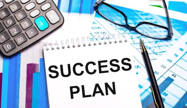 Pulpit zawiera kolorowe tabele, kalkulator, okulary, długopis i notatnik z napisem plan sukcesu