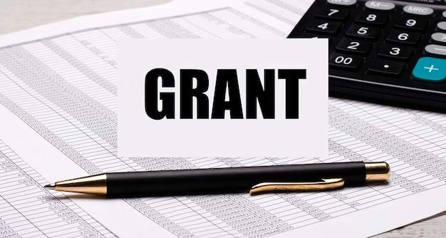 Pulpit zawiera raporty, kalkulator, długopis i białą kartę z napisem grant