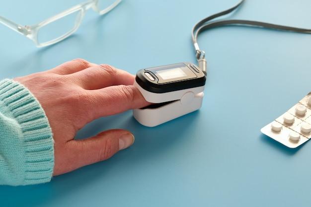 Pulsoksymetr, cyfrowe urządzenie do pomiaru palca w celu nasycenia tlenem. zmniejszone natlenienie - nagły objaw zapalenia płuc, na przykład spowodowany przez koronawirusa. urządzenie na kobiecej dłoni rasy białej.