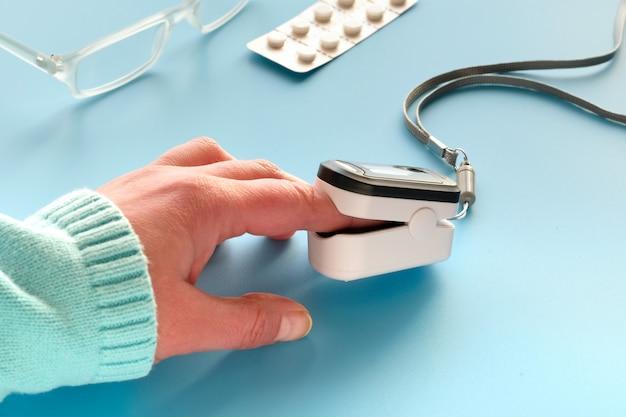 Pulsoksymetr, cyfrowe urządzenie do pomiaru palca w celu nasycenia tlenem. zmniejszone natlenienie - nagły objaw zapalenia płuc spowodowanego grypą lub nowym koronawirusem. urządzenie na kobiecej dłoni rasy białej.