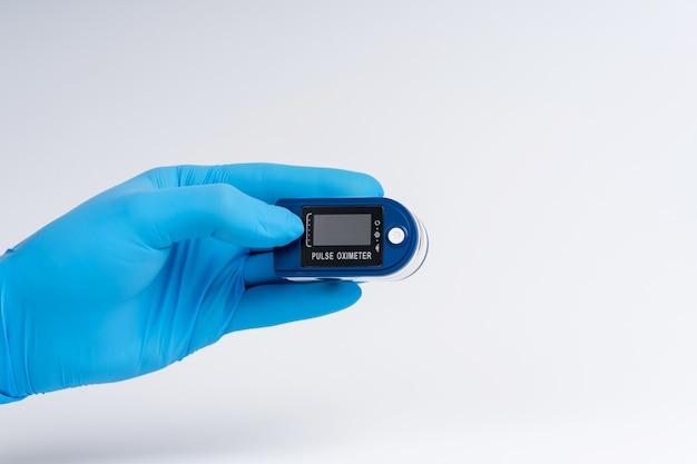 Pulsoksymetr na białym tle. ręka w rękawicy medycznej trzyma urządzenie do diagnostyki zdrowia.