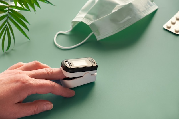 Pulsoksymetr przenośne urządzenie cyfrowe do pomiaru nasycenia tlenem osoby. zmniejszenie natlenienia jest nagłym objawem zapalenia płuc wymagającym pilnej hospitalizacji.