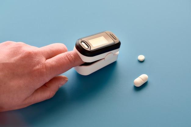 Pulsoksymetr przenośne urządzenie cyfrowe do pomiaru nasycenia tlenem osoby. zmniejszenie natlenienia jest objawem nagłym, ciężką postacią wirusowego zapalenia płuc covid-19