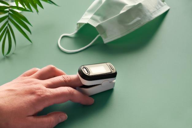 Pulsoksymetr przenośne urządzenie cyfrowe do pomiaru nasycenia tlenem osoby. zmniejszenie natlenienia jest oznaką nagłego wirusowego zapalenia płuc covid-19 wymagającą natychmiastowej pomocy medycznej.