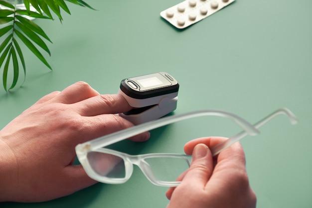 Pulsoksymetr przenośne urządzenie cyfrowe do pomiaru nasycenia tlenem osoby. zmniejszenie natlenienia to nagły objaw wirusowego zapalenia płuc covid-19, wymagający pilnej pomocy medycznej.