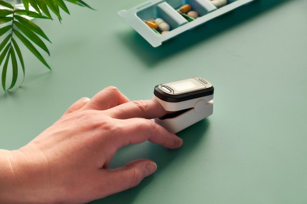 Pulsoksymetr przenośne urządzenie cyfrowe do pomiaru nasycenia tlenem osoby. zmniejszone natlenienie jest nagłym objawem zapalenia płuc wymagającym natychmiastowej pomocy medycznej.