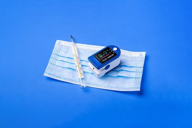 Pulsoksymetr w pobliżu termometru i maski medycznej, koncepcja monitorowania opieki zdrowotnej