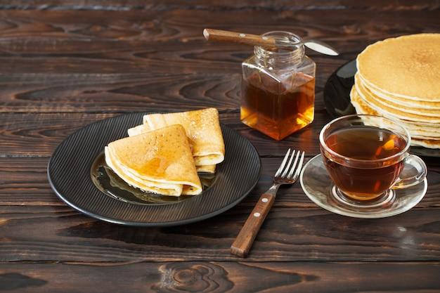 Puncakes z miodem i filiżanką herbaty na starym drewnianym stole