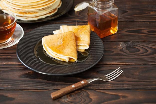 Puncakes z miodem i filiżanką herbaty na starym drewnianym tle