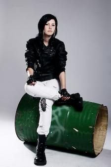 Punk dziewczyna siedzi na metalowej beczce