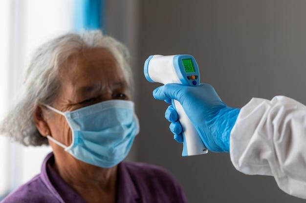 Punkt kontrolny koronawirusa, lekarze sprawdzający temperaturę starzejącej się pacjentki, która jest zagrożona infekcją wirusem koronowym [covid-19].