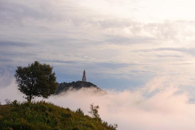 Punkt widokowy na szczycie góry pokrytej mgłą na całym obszarze. wraz ze słońcem o poranku.