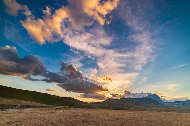 Punkt widokowy na zachód słońca na skalistych górach, wyżynach i pastwiskach. campo imperatore, gran sasso, apeniny, włochy. kolorowe chmury na niebie na dramatycznym grzbiecie górskim.