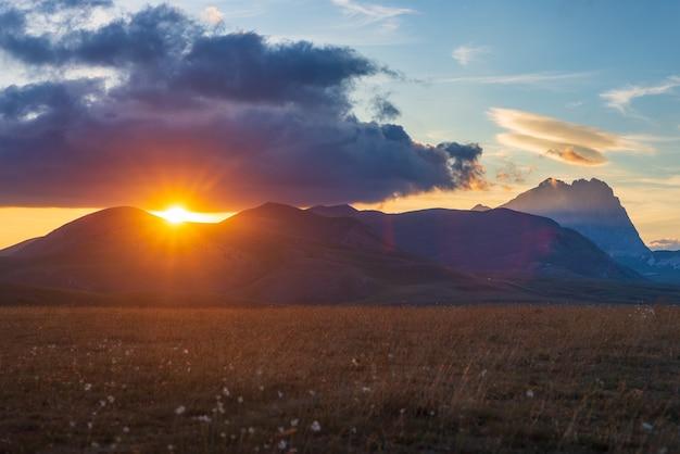 Punkt widokowy na zachód słońca na skalistych górach, wyżynach i pastwiskach. campo imperatore, gran sasso, apeniny, włochy. promienie słońca i kolorowe chmury na niebie na dramatycznym grzbiecie górskim.