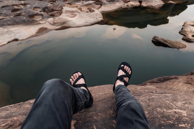 Punkt widzenia nogi człowieka w butach turystycznych siedzi na skalnym klifie w wielkim kanionie