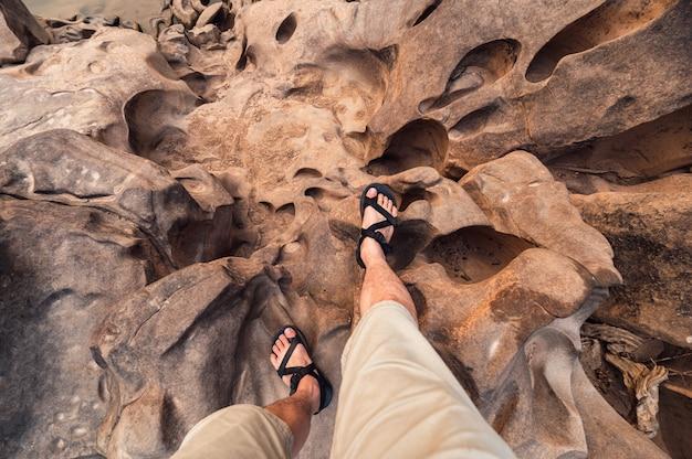 Punkt widzenia nogi człowieka z butów turystycznych stojących na chropowatej skale wielkiego kanionu w tajlandii