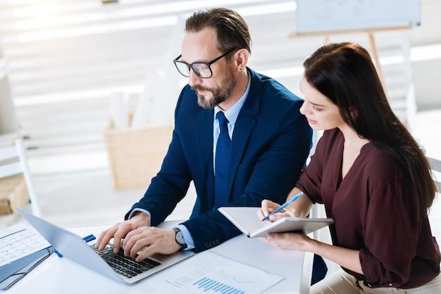 Punkty pracy. widok z góry skupiony uważny dwóch kolegów patrząc na ekran, podczas gdy mężczyzna pisze i kobieta trzyma notatnik