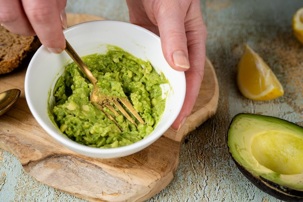Puree z awokado. bliska kobiece ręce zacierania awokado widelcem w białej płytce. koncepcja zdrowej żywności. wysokie tłuszcze nasycone mogą pomóc w utrzymaniu zdrowego poziomu cholesterolu. wegańskie jedzenie