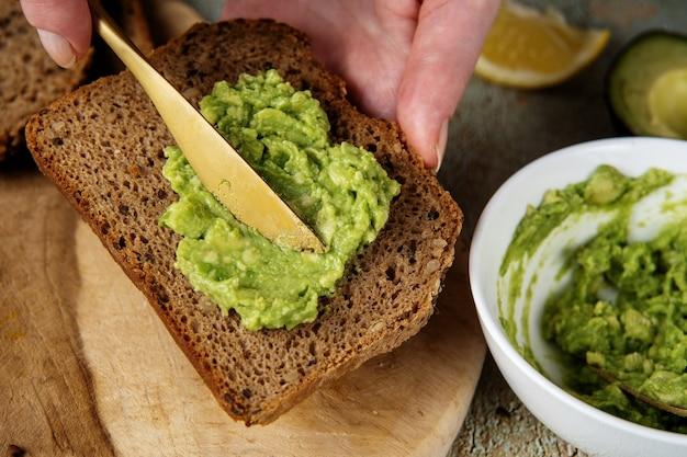 Puree z awokado. rozprowadzanie mielonego awokado na zdrowej kromce chleba. koncepcja zdrowej żywności wegańskiej. wysokie tłuszcze nasycone mogą pomóc w utrzymaniu zdrowego poziomu cholesterolu