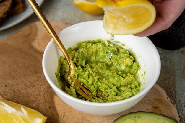 Puree z awokado. wyciskanie soku z cytryny na talerz z mielonym awokado. koncepcja zdrowej żywności wegańskiej. wysokie tłuszcze nasycone mogą pomóc w utrzymaniu zdrowego poziomu cholesterolu