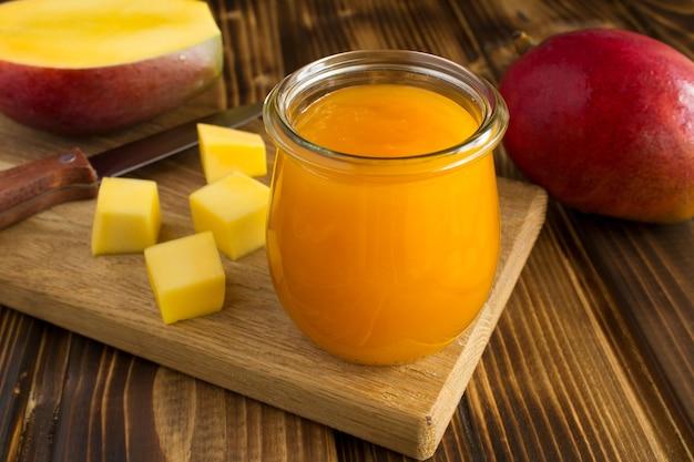 Puree z mango i składnikiem na drewnianej desce do krojenia