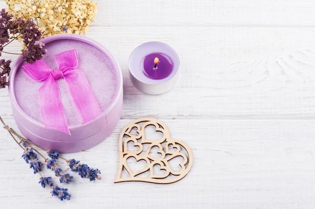 Purpura kwiaty i zaświecająca świeczka na bielu stole